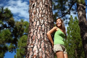 Beautiful smiling woman in summer forest looking at copy space. Image from pine tree forest near Vilaflor, Tenerife, Canary Islands.